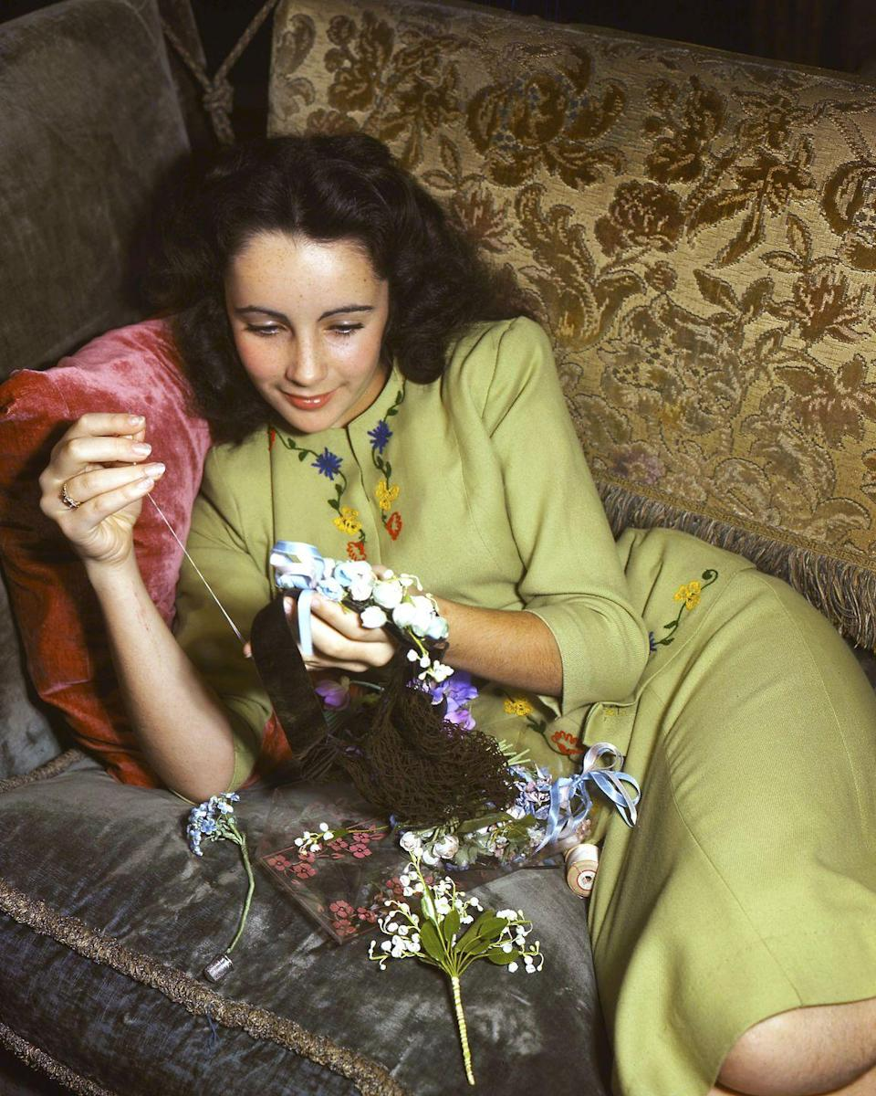 <p>The actress is seen sewing preserved flowers into a hair piece in 1950. </p>