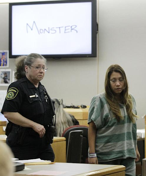 "The word ""Monster"" shown on an overhead display that prosecutor Eren Price, not pictured, wrote is shown on a large display in court as a Dallas Sheriffs deputy escorts Elizabeth Escalona, 23, back to her seat in court during the sentencing phase of her trial Thursday, Oct. 11, 2012, in Dallas. Escalona, a mother of five facing prison time for beating her 2-year-old daughter and gluing the toddler's hands to a wall, admitted to using drugs and alcohol while out on bond after her arrest. (AP Photo/Tony Gutierrez)"