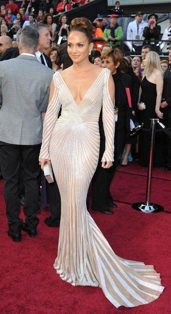 Entertainer Jennifer Lopez arrives for the Academy Awards wearing a white a gold dress with plunge neckline.