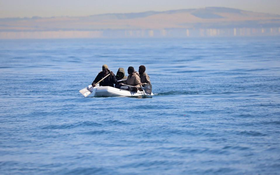 Four men, some using shovels as paddles, use a small dinghy to cross the English Channel on August 7, 2020 - GETTY IMAGES