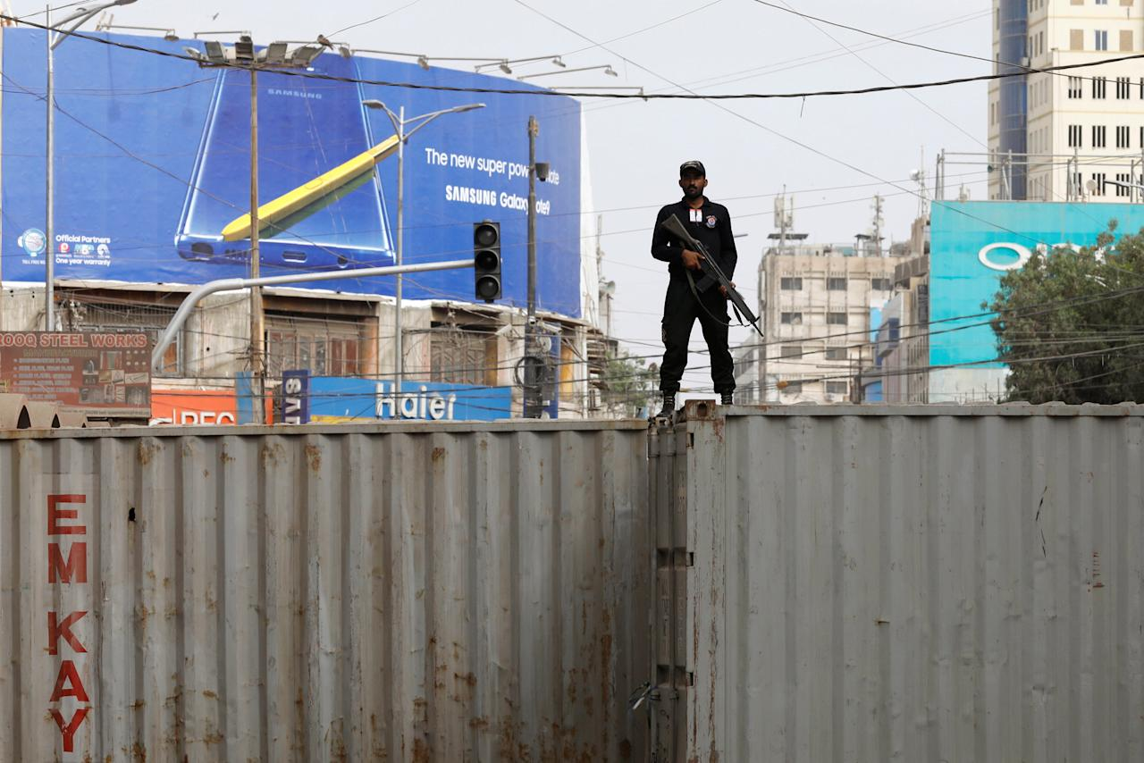 A policeman stands guard on a shipping container used to block roads, as added security is put in place, during a religious procession to mark Ashura in Karachi, Pakistan, September 21, 2018. REUTERS/Akhtar Soomro