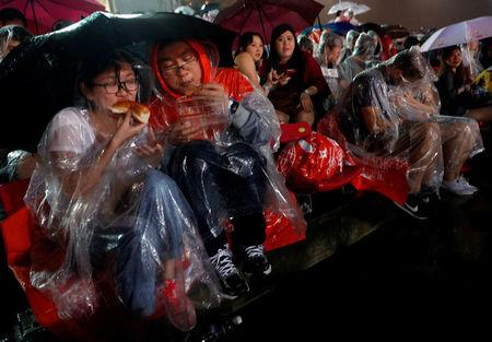 FILE PHOTO: People wait in the rain to watch the New Year fireworks at Marina Bay in Singapore December 31, 2017. REUTERS/Edgar Su/File Photo