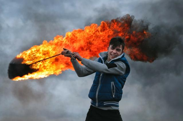 In this photo taken on Sunday, March 10, 2019, a young man spins a burning tire on a metal chain, during a ritual marking the upcoming Clean Monday, the beginning of the Great Lent, 40 days ahead of Orthodox Easter, on the hills surrounding the village of Poplaca, in central Romania's Transylvania region. Romanian villagers burn piles of used tires then spin them in the Transylvanian hills in a ritual they believe will ward off evil spirits as they begin a period of 40 days of abstention, when Orthodox Christians cut out meat, fish, eggs, and dairy. (AP Photo/Vadim Ghirda)