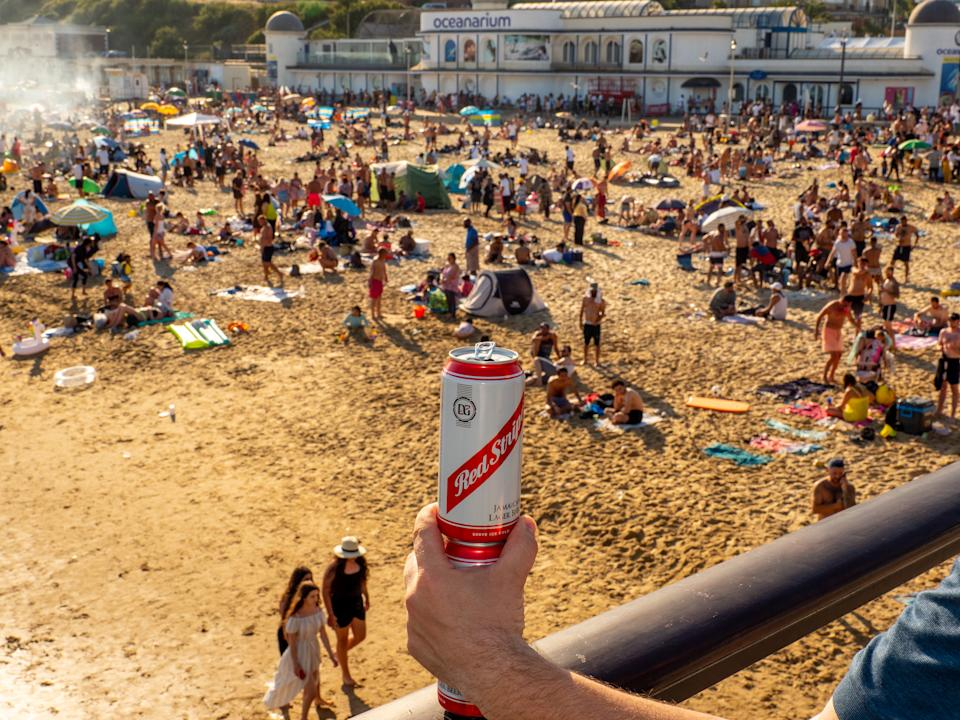 BOURNEMOUTH, UNITED KINGDOM - JUNE 25:  A can of lager is held as a crowd forms on Bournemouth beach on June 25,2020 in Bournemouth,England. A major incident was declared after thousands of people defied advice to stay away and descended on Bournemouth beach on the hottest day of the year so far. Services were overstretched as visitors arrived in large volumes, with Bournemouth, Christchurch and Poole Council issuing a record 558 parking enforcement fines. (Photo by Peter Dench/Getty Images)