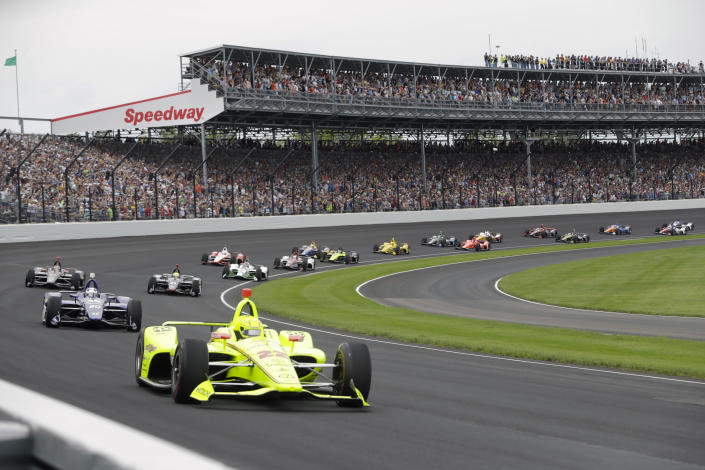 """FILE - In this May 26, 2019, file photo, Simon Pagenaud, of France, leads the field through the first turn on the start of the Indianapolis 500 IndyCar auto race at Indianapolis Motor Speedway in Indianapolis. The Indianapolis 500 will be the largest sporting event since the start of the pandemic with 135,000 spectators permitted to attend """"The Greatest Spectacle in Racing"""" next month. Indianapolis Motor Speedway said Wednesday, April 21, 2021, it worked with the Marion County Public Health Department to determine 40% of venue capacity can attend the May 30 race. (AP Photo/Darron Cummings, File)"""