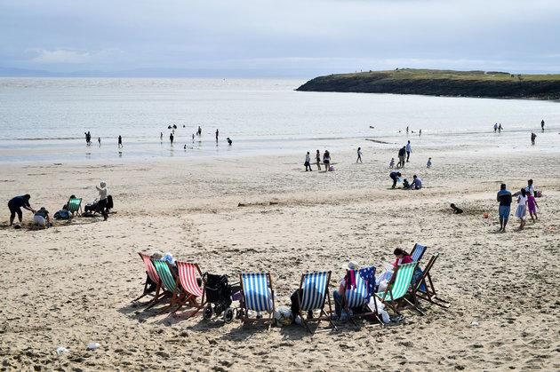 A bright spell hits beachgoers at Barry Island, Wales, on Saturday.