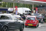 Drivers queue for fuel at a petrol station in Birmingham, England, Tuesday, Sept. 28, 2021. Long lines of vehicles have formed at many gas stations around Britain since Friday, causing spillover traffic jams on busy roads. (AP Photo/Jacob King)