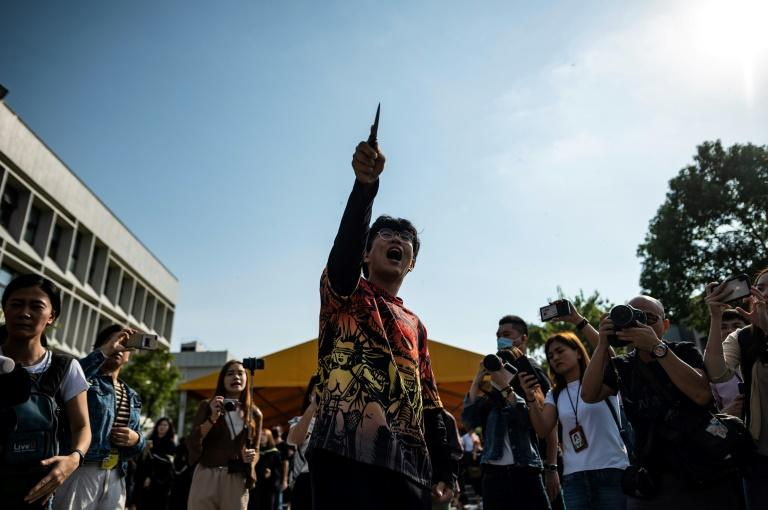 A Mandarin Chinese-speaking man - presumably a pro-Beijing supporter - points a knife at student protesters at the Chinese University of Hong Kong (AFP Photo/Philip FONG)
