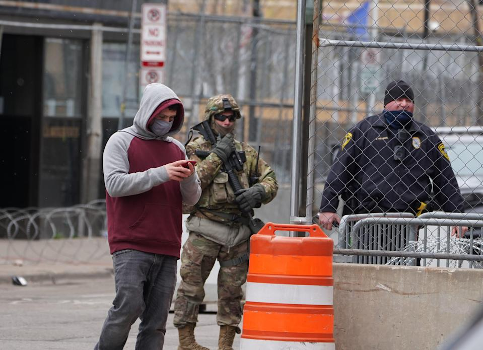A member of the Minnesota National Guard and a police officer patrol an intersection in downtown Minneapolis shortly before jurors were set to begin deliberations in the murder trial of former police officer Derek Chauvin.