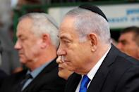 Israeli Prime Minister Benjamin Netanyahu looks on as he sits next to Benny Gantz, leader of Blue and White party, during a memorial ceremony for late Israeli President Shimon Peres, at Mount Herzl in Jerusalem