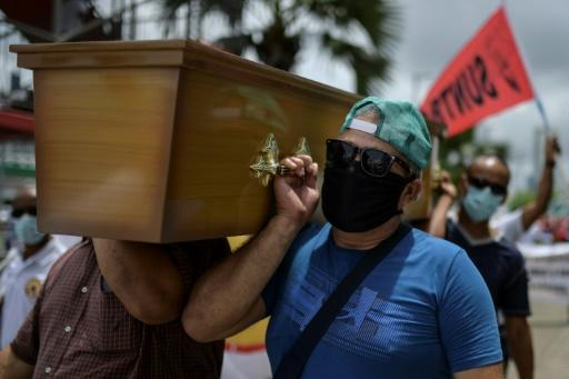 Trade union members in Panama City carry a mock coffin in protest against government measures to reopen the economy, saying it will lead to a spike in coronavirus infections and deaths