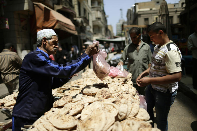 FILE - In this Thursday, June 27, 2013 file photo, Egyptians buy bread at a popular market in Cairo, Egypt. As the streets once again fill with protesters eager to oust the president and Islamists determined to keep him in power, Egyptians are preparing for the worst: days or weeks of urban chaos that could turn a loved one into a victim. Households already beset by power cuts, fuel shortages and rising prices are stocking up on goods in case the demonstrations drag on. Businesses near protest sites are closing until crowds subside. Fences, barricades and walls are going up near homes and key buildings. And local communities are organizing citizen patrols in case security breaks down. (AP Photo/Hassan Ammar, File)