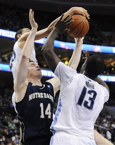 Notre Dame's Scott Martin (14) has his shot blocked by Villanova's Mouphtaou Yarou (13) and Maurice Sutton (25) in the first half of an NCAA college basketball game on Saturday, Feb. 18, 2012, in Philadelphia. (AP Photo/Michael Perez)