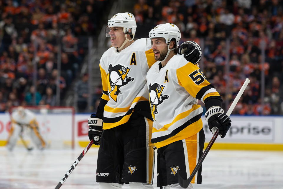 Pittsburgh Penguins' Kris Letang (58) celebrates his goal with Evgeni Malkin (71) during the third period of an NHL hockey game against the Edmonton Oilers on Friday, Dec. 20, 2019, in Edmonton, Alberta. (Codie McLachlan/The Canadian Press via AP)