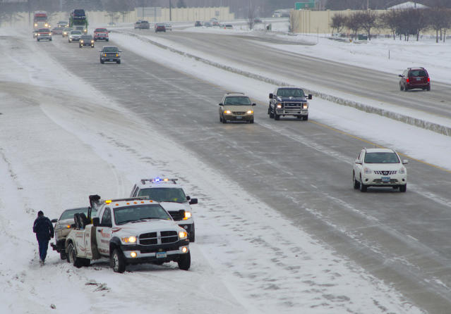 A tow truck operator prepares to haul away a car involved in an accident on Interstate 94 in Fargo, N.D. on Monday, March 4, 2013. Overnight snow made travel treacherous across much of the upper Midwest. (AP Photo/Minnesota Public Radio, Nathaniel Minor)