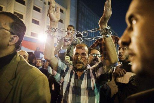 An Egyptian man with his wrists bound by a chain joins thousands of Egyptian protesters as they rally and shout slogans