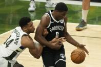 Milwaukee Bucks' Giannis Antetokounmpo and Brooklyn Nets' Reggie Perry battle for a loose ball during the second half of Game 4 of the NBA Eastern Conference basketball semifinals game Sunday, June 13, 2021, in Milwaukee. (AP Photo/Morry Gash)