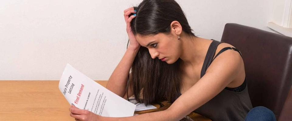 young student worried over un-paid bills and student loan