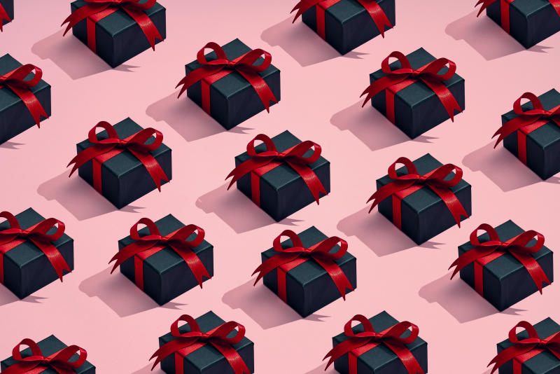 A group of gifts are placed in a pattern on a colored background