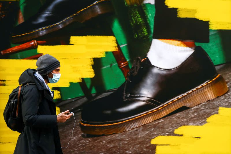 """FILE PHOTO: A woman walks past the window of a """"Dr Martens"""" shoe shop amid the coronavirus disease (COVID-19) outbreak in central Madrid"""