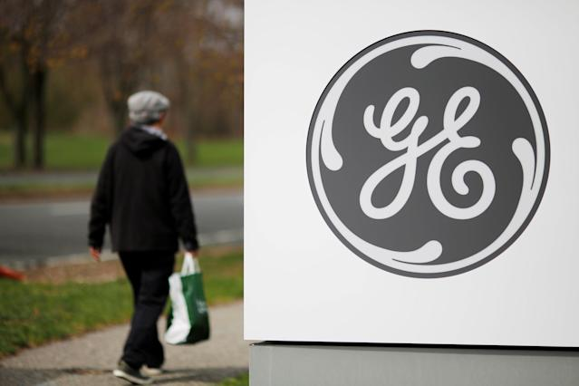 A pedestrian walks past a General Electric (GE) facility in Medford, Massachusetts, U.S., April 20, 2017. GE will be leaving the Dow next week after more than 110 years of continuous membership in the index. REUTERS/Brian Snyder/File Photo