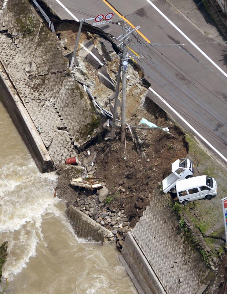 A road along a river is partially collapsed in Yame, Fukuoka Prefecture, Japan, Sunday, July 15, 2012. Heavy rain triggered flash floods and mudslides in southern Japan this week, killing over two dozens of people. (AP Photo/Kyodo News) JAPAN OUT, MANDATORY CREDIT, NO LICENSING IN JAPAN, CHINA, HONG KONG, SOUTH KOREA AND FRANCE