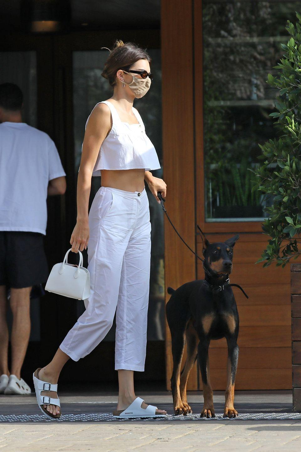 <p>The model was spotted with her dobermann Six, heading for dinner in Malibu with friends on August 2nd. Wearing a mask, and an all-white outfit in the form of linen trousers, a peplum crop top and Birkenstocks, the model looked both chic and Covid-safe.</p>