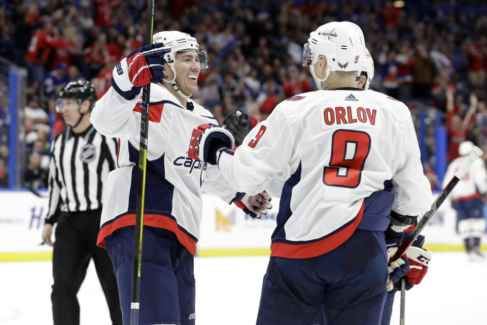Washington Capitals right wing T.J. Oshie (77) celebrates his goal against the Tampa Bay Lightning with defenseman Dmitry Orlov (9) during the third period of an NHL hockey game Saturday, Dec. 14, 2019, in Tampa, Fla. (AP Photo/Chris O'Meara)