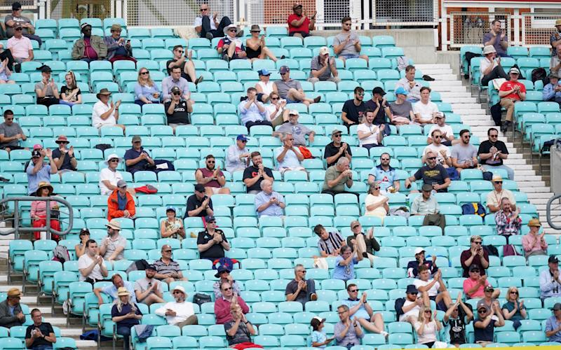Spectators observe social distancing in the stands during the friendly match at the Kia Oval, London. - PA