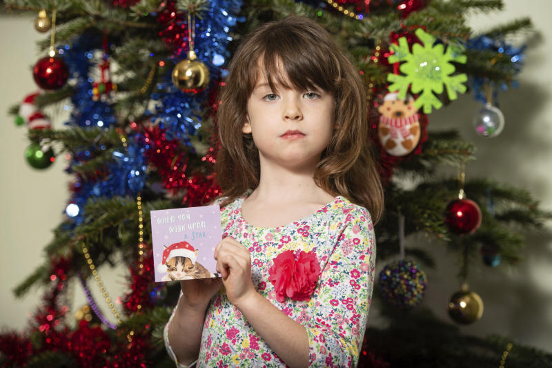 Florence Widdicombe, 6, poses with a Tesco Christmas card from the same pack as a card she found containing a message from a Chinese prisoner, in London, Sunday, Dec. 22, 2019. The U.K.-based grocery chain Tesco has halted production at a factory in China after a British newspaper said it used forced labor to produce charity Christmas cards. Tesco said Sunday it had stopped production and launched an investigation after the Sunday Times newspaper raised questions about the factory's labor practices. (Dominic Lipinski/PA via AP)
