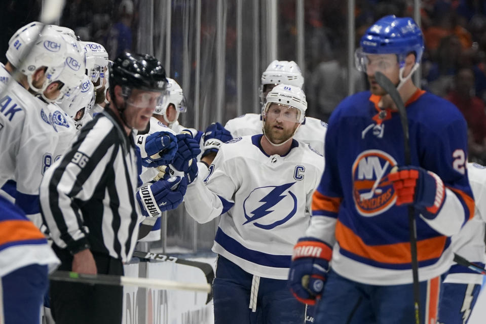 Tampa Bay Lightning center Steven Stamkos (91) high fives teammates after Tampa Bay Lightning center Brayden Point (not pictured) scored against the New York Islanders during the second period of Game 3 of the NHL hockey Stanley Cup semifinals, Thursday, June 17, 2021, in Uniondale, N.Y. (AP Photo/Frank Franklin II)