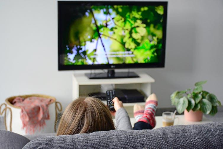 Young woman watching subtitled programme