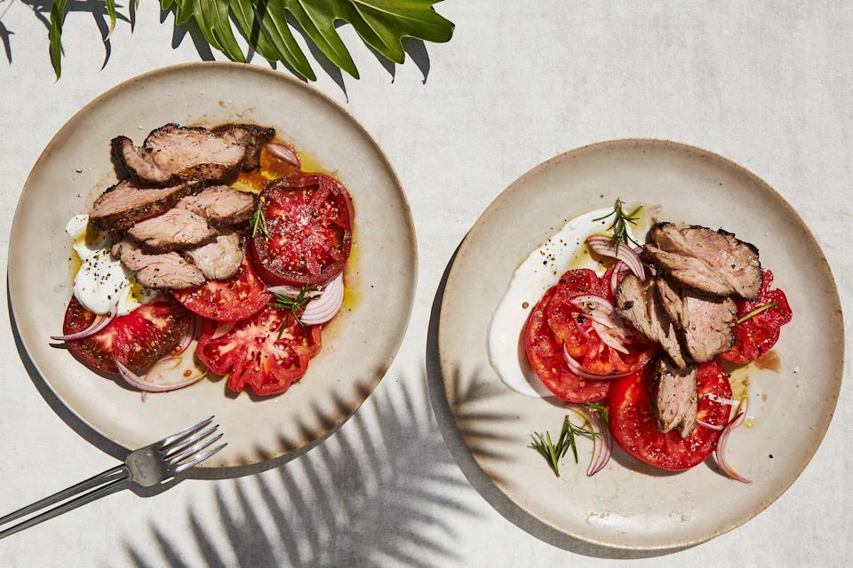 """Lamb shoulder: not just for braising! In this recipe, separating the shoulder into a few smaller-size pieces before marinating makes it less unwieldy on the grill and allows you to monitor the internal temperature more easily. Slice and season the tomatoes ahead of time so they'll release their juices. <a href=""""https://www.epicurious.com/recipes/food/views/grilled-rosemary-lamb-with-juicy-tomatoes?mbid=synd_yahoo_rss"""" rel=""""nofollow noopener"""" target=""""_blank"""" data-ylk=""""slk:See recipe."""" class=""""link rapid-noclick-resp"""">See recipe.</a>"""