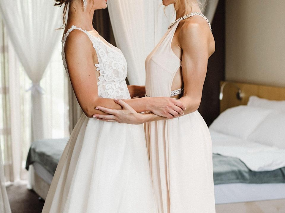 Two brides in white dresses looking at each other.