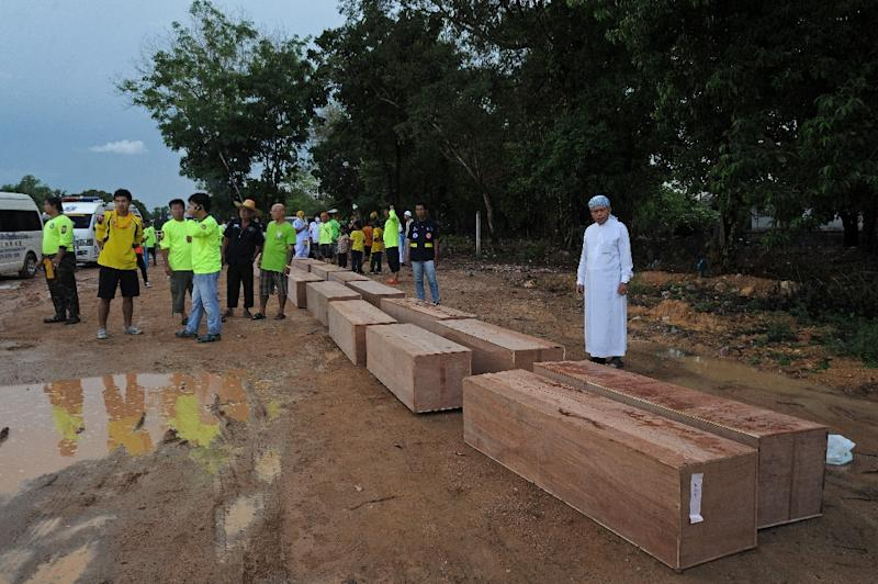 Thai rescue workers bring coffins containing the human remains of migrants exhumed from a jungle camp in the southern Songkhla province, on May 3, 2015 (AFP Photo/Madaree Tohlala)