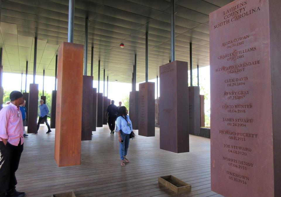 FILE - In this April 28, 2018, file photo, visitors look at markers bearing the names of lynching victims at the National Memorial for Peace and Justice in Montgomery, Ala. Some states have already criminalized the display of nooses, including Louisiana, Virginia, California, New York and Connecticut. Oregon's bill, if passed by the Democrat-controlled Legislature and signed by the Democratic governor, will make intimidation by display of a noose a misdemeanor punishable by up to a year in prison and a $6,250 fine. (AP Photo/Beth J. Harpaz, File)