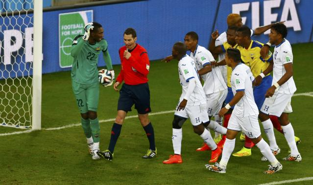 Referee Benjamin Williams of Australia walks beside Ecuador's Alexander Dominguez (L) as Honduras national soccer players argue with him during their 2014 World Cup Group E soccer match at the Baixada arena in Curitiba June 20, 2014. Jerry Bengtson of Honduras had hit the ball into the goal, but this was disallowed by Williams as it was a handball. REUTERS/Amr Abdallah Dalsh (BRAZIL - Tags: SOCCER SPORT WORLD CUP TPX IMAGES OF THE DAY) TOPCUP