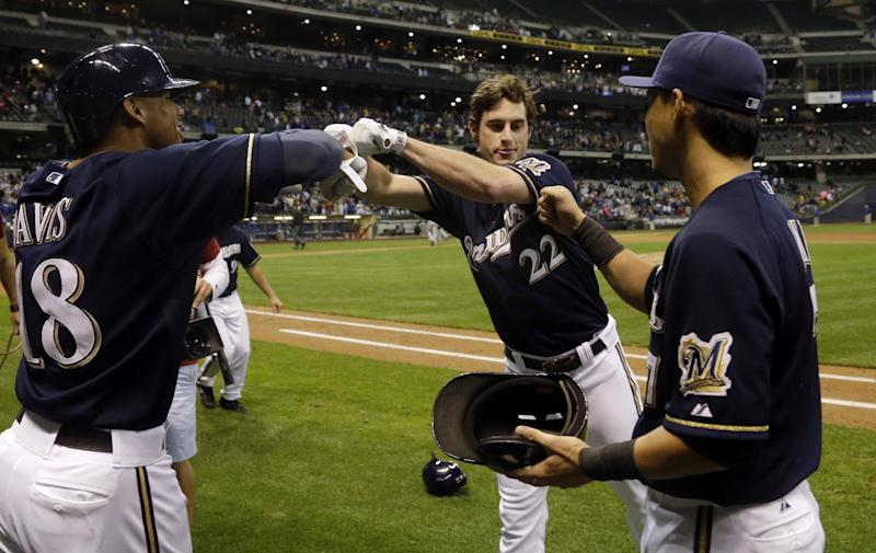 Milwaukee Brewers' Logan Schafer (22) is congratulated by Khris Davis (18) and Norichika Aoki after a baseball game against the Chicago Cubs, Tuesday, Sept. 17, 2013, in Milwaukee. Jeff Bianchi scored on a suicide squeeze bunt by Schafer. The Brewers won 4-3. (AP Photo/Morry Gash)