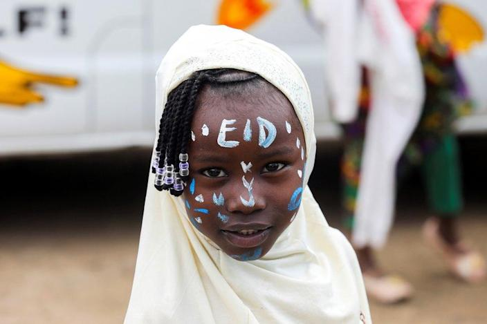 """A girl has the word """"Eid""""  smeared on his forehead with face paint."""