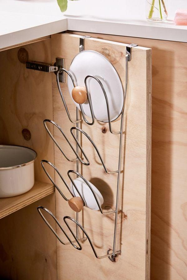 """<p>Double your storage space with this <a href=""""https://www.popsugar.com/buy/Over--Cabinet-Lid-Holder-481778?p_name=Over-the-Cabinet%20Lid%20Holder&retailer=urbanoutfitters.com&pid=481778&price=29&evar1=casa%3Auk&evar9=46515492&evar98=https%3A%2F%2Fwww.popsugar.com%2Fhome%2Fphoto-gallery%2F46515492%2Fimage%2F46516100%2FOver--Cabinet-Lid-Holder&list1=shopping%2Corganizing%2Corganization%2Ckitchen%20organization%2Ckitchens%2Chome%20shopping%2Curban%20oufitters&prop13=api&pdata=1"""" rel=""""nofollow"""" data-shoppable-link=""""1"""" target=""""_blank"""" class=""""ga-track"""" data-ga-category=""""Related"""" data-ga-label=""""https://www.urbanoutfitters.com/shop/over-the-cabinet-lid-holder?category=dinnerware&amp;color=007&amp;type=REGULAR"""" data-ga-action=""""In-Line Links"""">Over-the-Cabinet Lid Holder</a> ($29).</p>"""