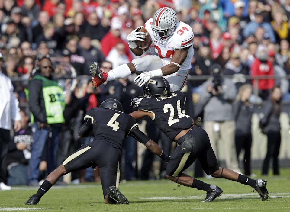 Ohio State running back Carlos Hyde, top, leaps over Purdue safety Taylor Richards (4) and defensive back Frankie Williams during the first half of an NCAA college football game in West Lafayette, Ind., Saturday, Nov. 2, 2013. (AP Photo/Michael Conroy)