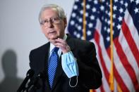 FILE PHOTO: Senate Majority Leader McConnell holds a face mask while participating in a news conference at the U.S. Capitol in Washington