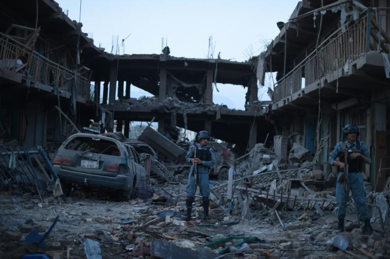 Afghan policemen stand gaurd at a market destroyed by a powerful truck bomb in Kabul on August 7, 2015