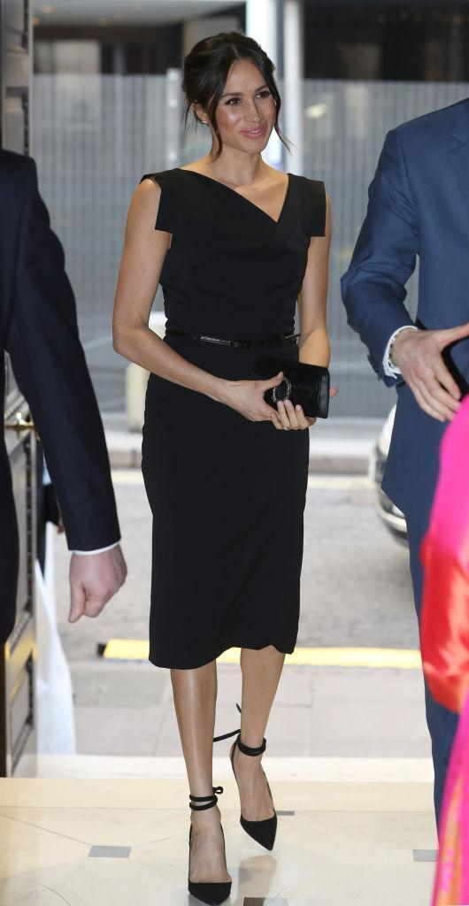 <p>For the Women's Empowerment reception, Meghan Markle opted for an LBD by Los Angeles-based brand, Halo and teamed the look with a Gucci clutch (which we need, asap). The former actress finished her newfound royal aesthetic with a pair of heels by Aquazzura and her trademark messy bun. <em>[Photo: Getty]</em> </p>