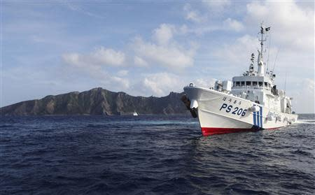 Japan Coast Guard vessel PS206 Houou sails in front of Uotsuri island, one of the disputed islands, called Senkaku in Japan and Diaoyu in China, in the East China Sea in this August 18, 2013 file photo. REUTERS/Ruairidh Villar/Files