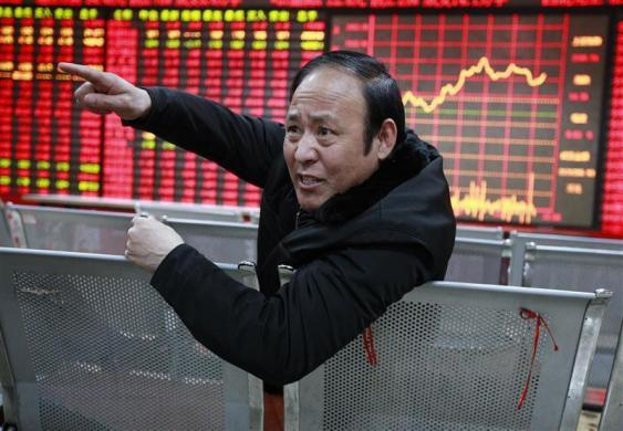 An investor gestures as he talks to a person in front of an electrical board showing stock information at a brokerage house in Huaibei, Anhui province, China February 22, 2012.