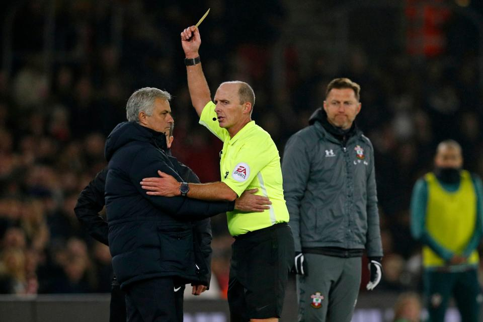Jose Mourinho is shown a yellow card by referee Mike Dean during Wednesday's Tottenham-Southampton match. (Photo by Adrian DENNIS / AFP)