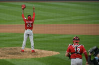 Cincinnati Reds pitcher Raisel Iglesias, left, reacts after striking out Minnesota Twins' Ehire Adrianza and winning a baseball game during the tenth inning Sunday, Sept. 27, 2020, in Minneapolis. (AP Photo/Craig Lassig)