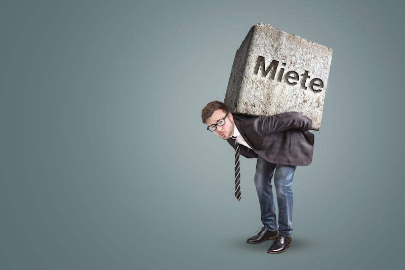 "Concept of a man bending under the burden of a high rent. He is actually carrying a massive stone on his back with the German word ""Miete"" on it - meaning ""rent""."