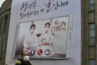 """A man wearing a face mask as a precaution against the coronavirus passes by a banner calling on residents to refrain from visiting families and relatives during the upcoming Lunar New Year holidays that start Feb. 11, in front of Seoul City Hall in Seoul, South Korea, Monday, Feb. 1, 2021. South Korea on Sunday said it will maintain elevated social distancing measures for at least two more weeks as health officials raise concerns about a possible surge in coronavirus infections surrounding the Lunar New Year holidays. The banner reads: """"It is a filial piety not to visit during the Lunar New Year holidays."""" (AP Photo/Ahn Young-joon)"""